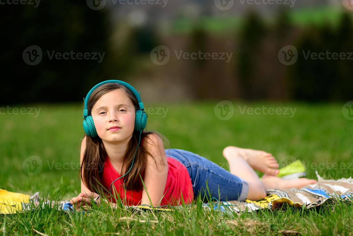 muito jovem, ouvindo música na natureza foto
