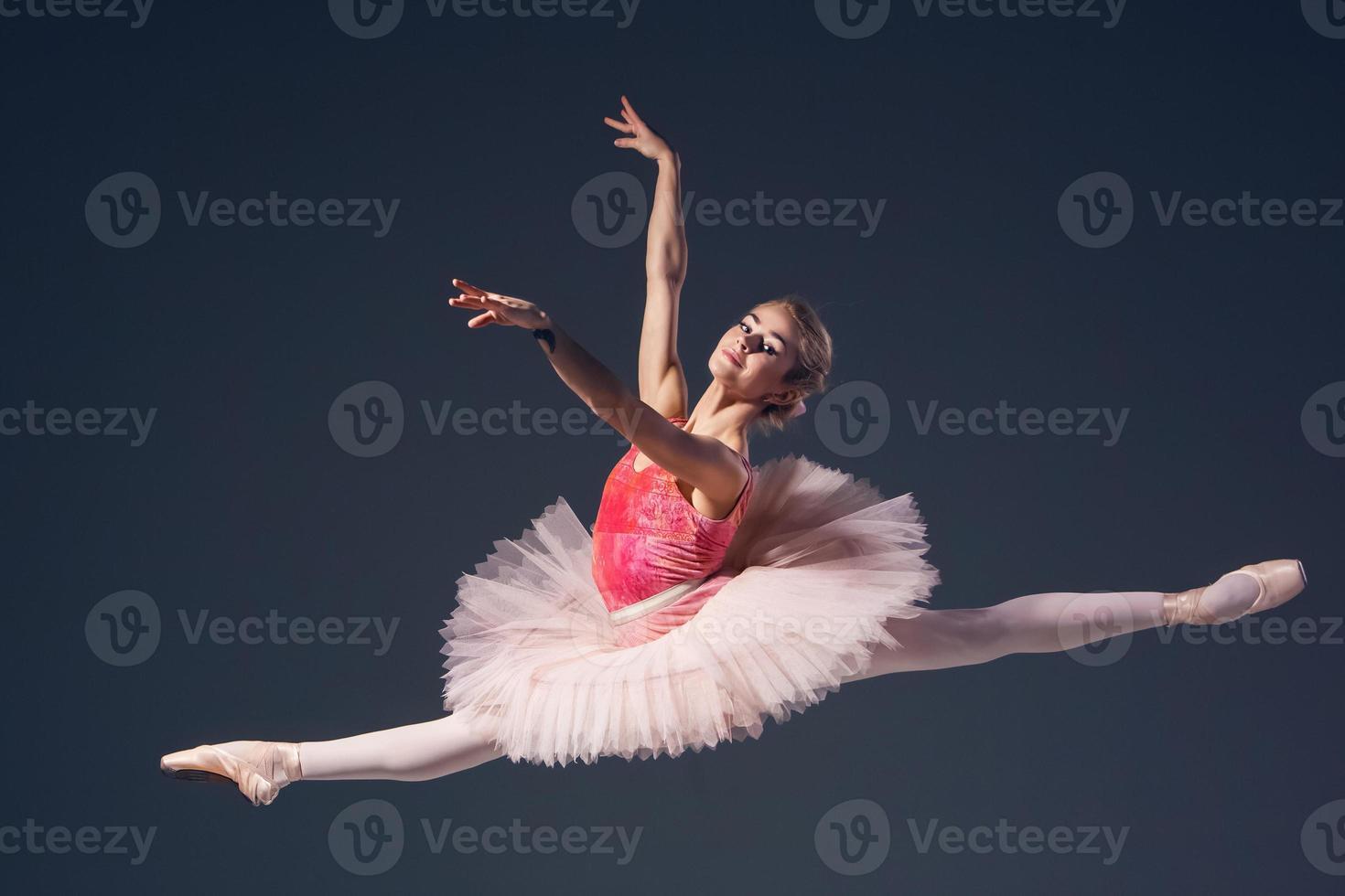 bela bailarina feminina em um fundo cinza foto