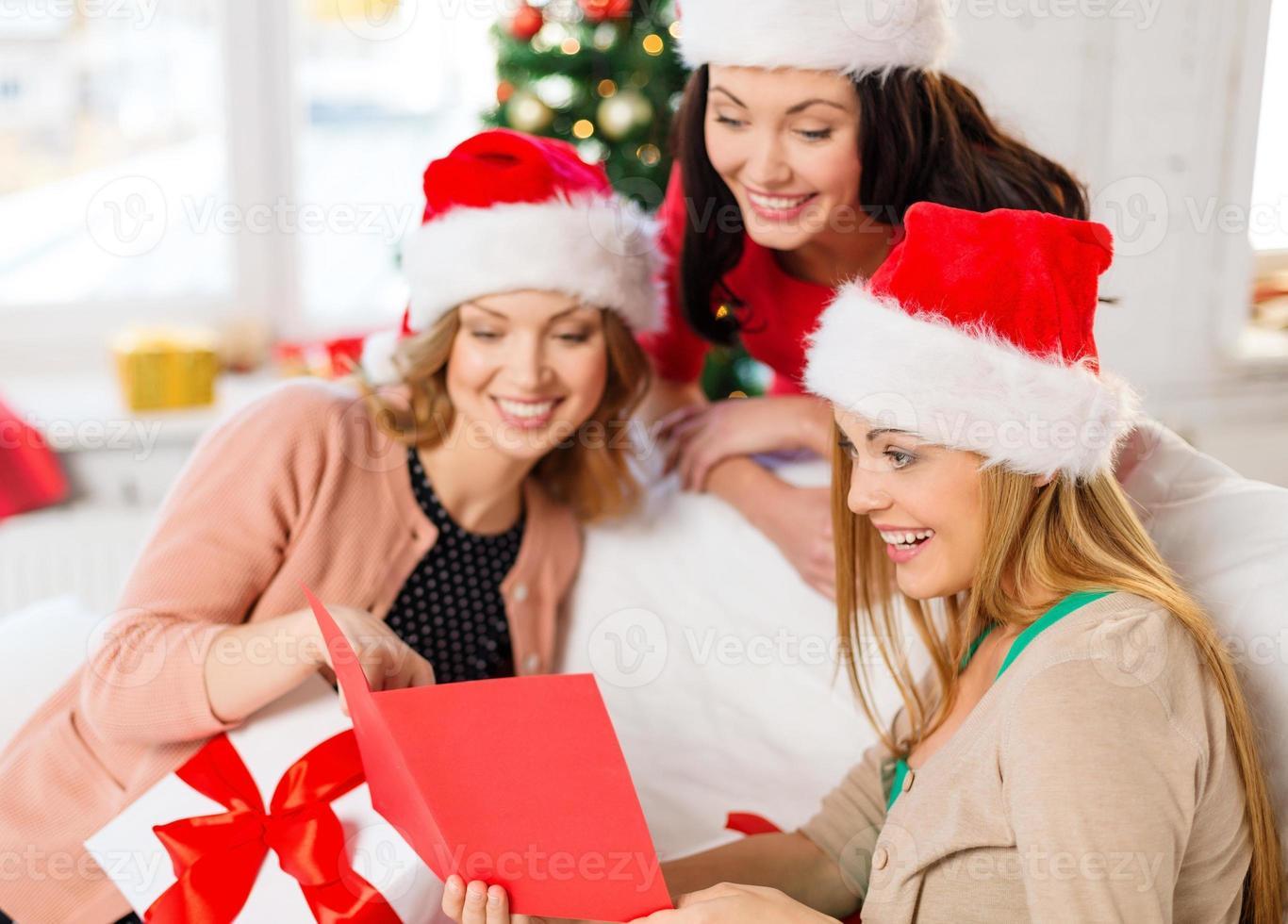 mulheres em chapéus de ajudante de Papai Noel com cartão e presentes foto