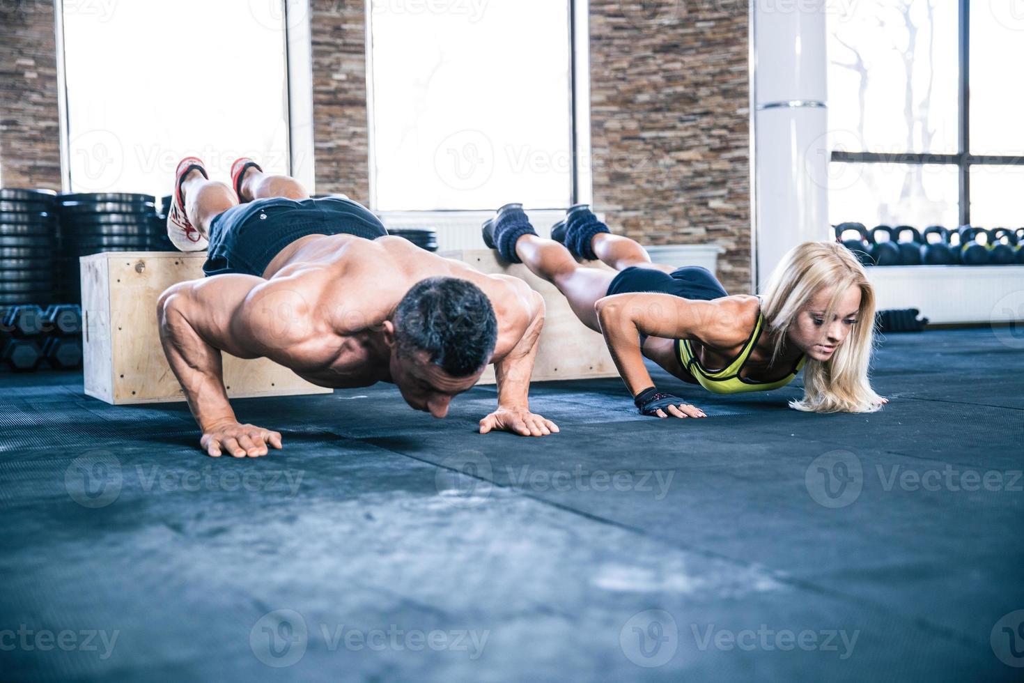 mulher e homem fazendo flexões foto