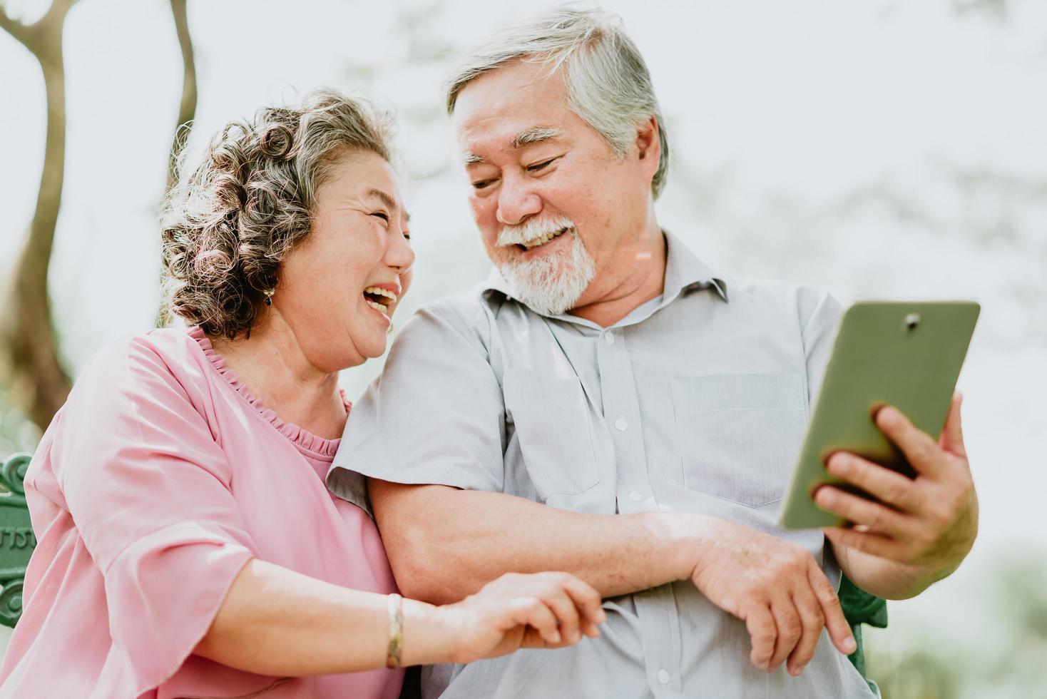 feliz casal sênior usando tablet foto