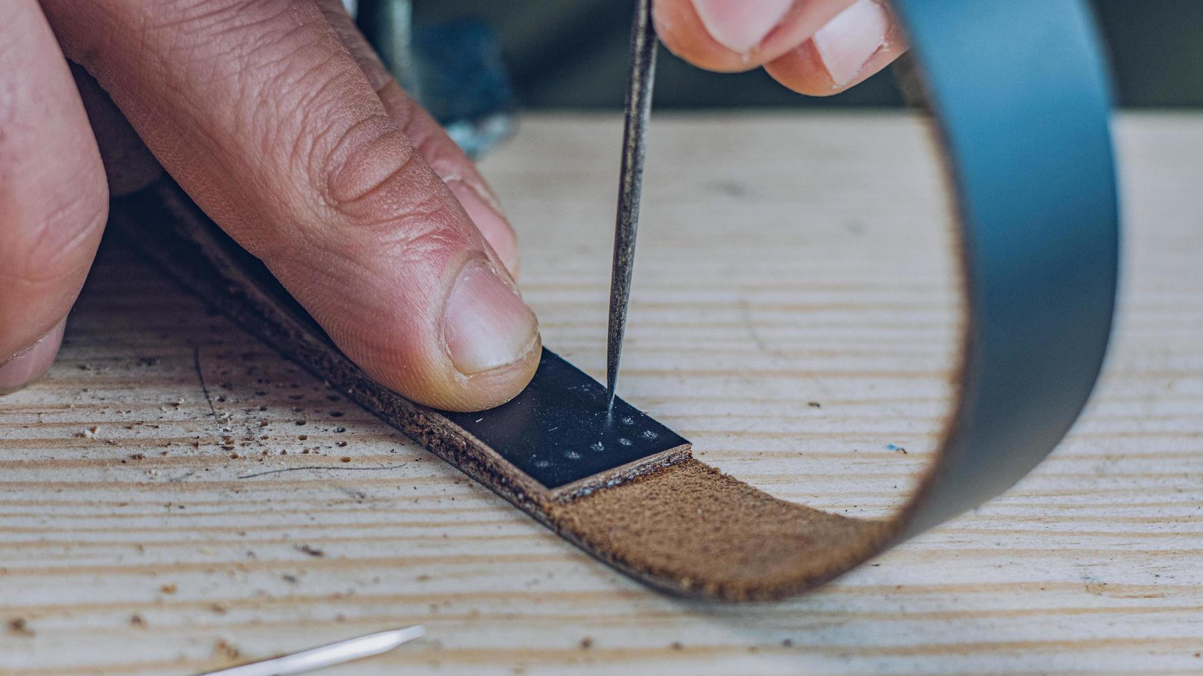 artesão fazendo uma pulseira de couro preta foto