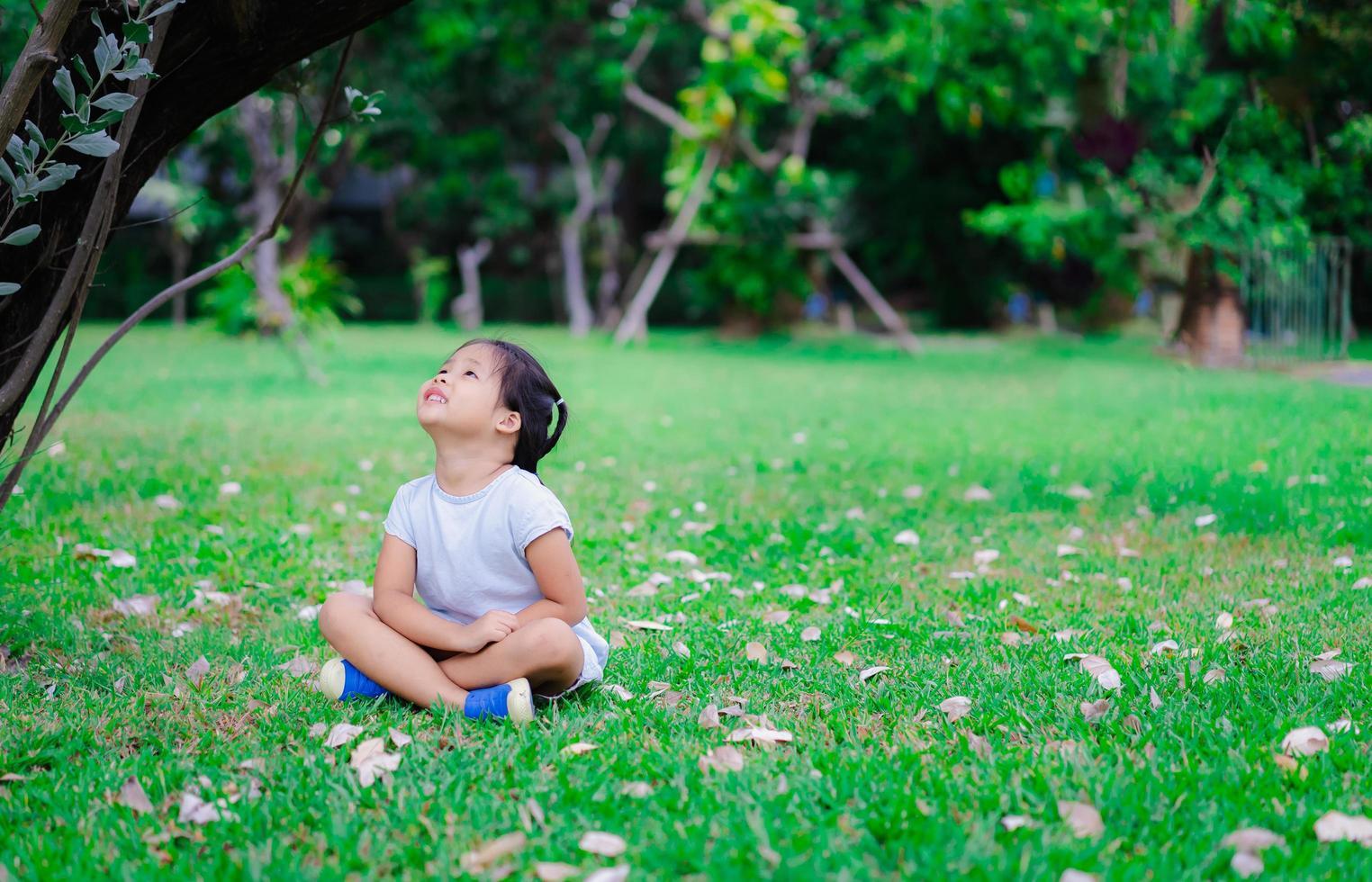 menina asiática bonitinha sentado no parque e olhando para cima foto