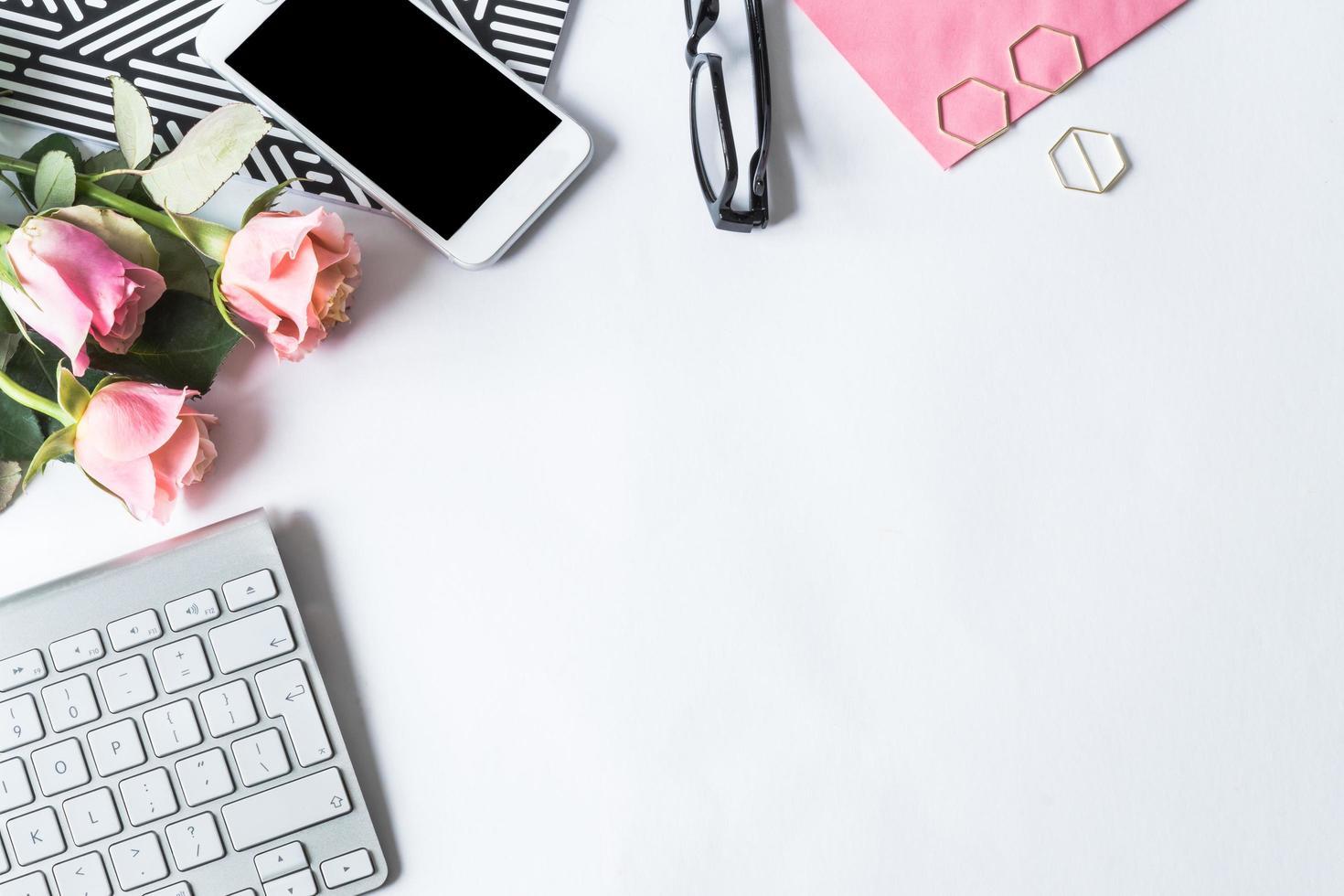 configuração plana com teclado, telefone, flores e óculos foto