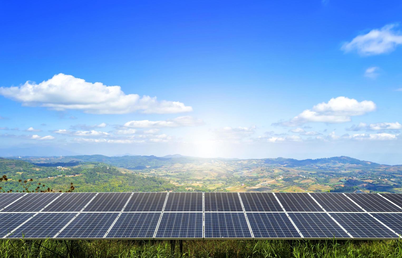 um campo de painel solar de energia fica no topo de uma montanha sob o céu azul foto