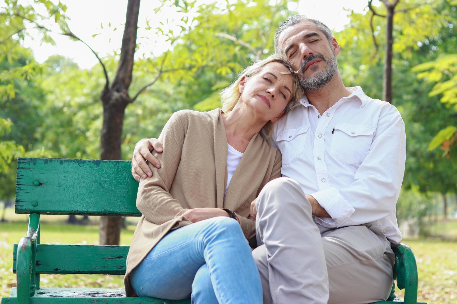 casal relaxando no banco do parque foto