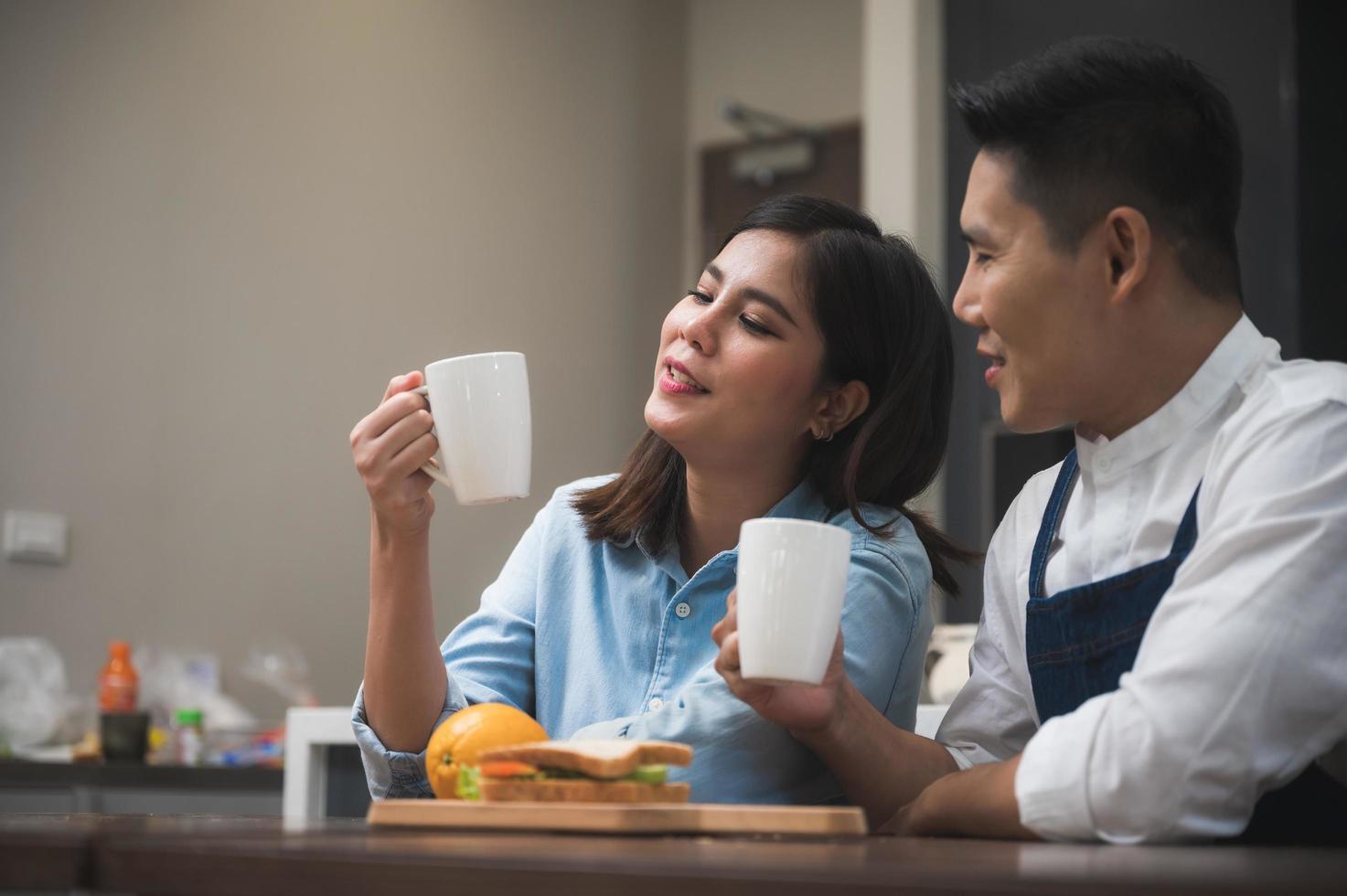 casal na cozinha sente-se sobre o café foto