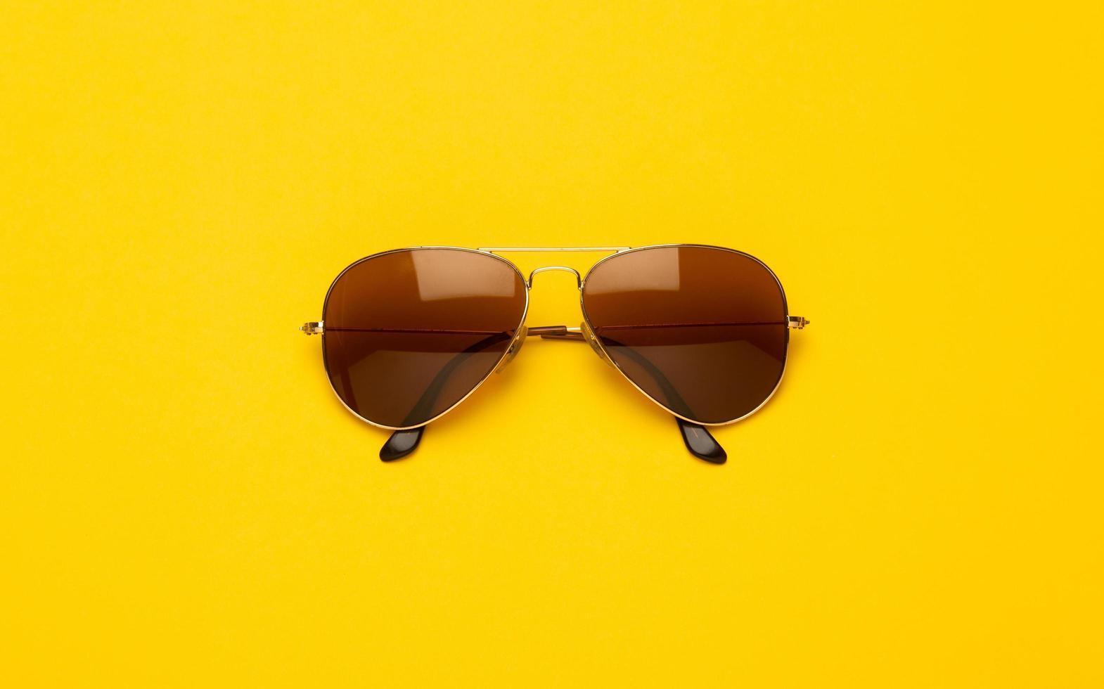 óculos de sol marrons sobre fundo amarelo foto