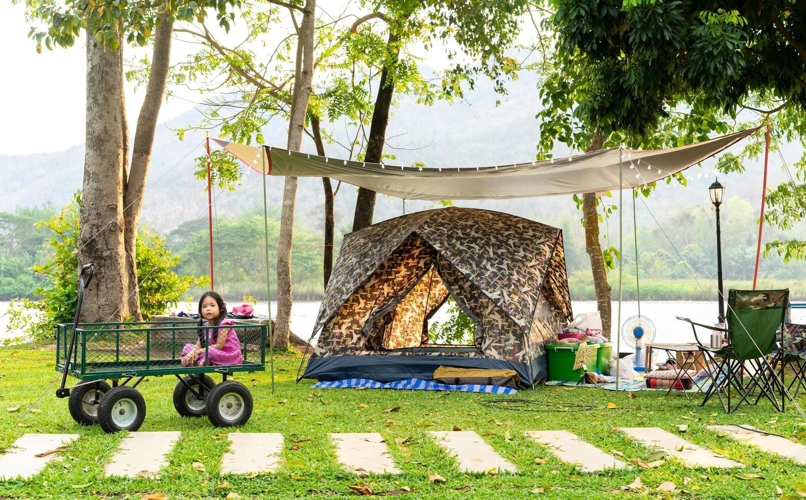 jovem menina asiática na carroça no parque de campismo foto