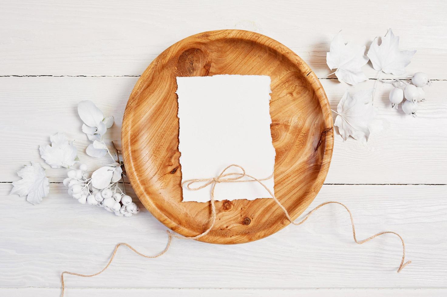 papel em branco na tigela de madeira na mesa de madeira foto