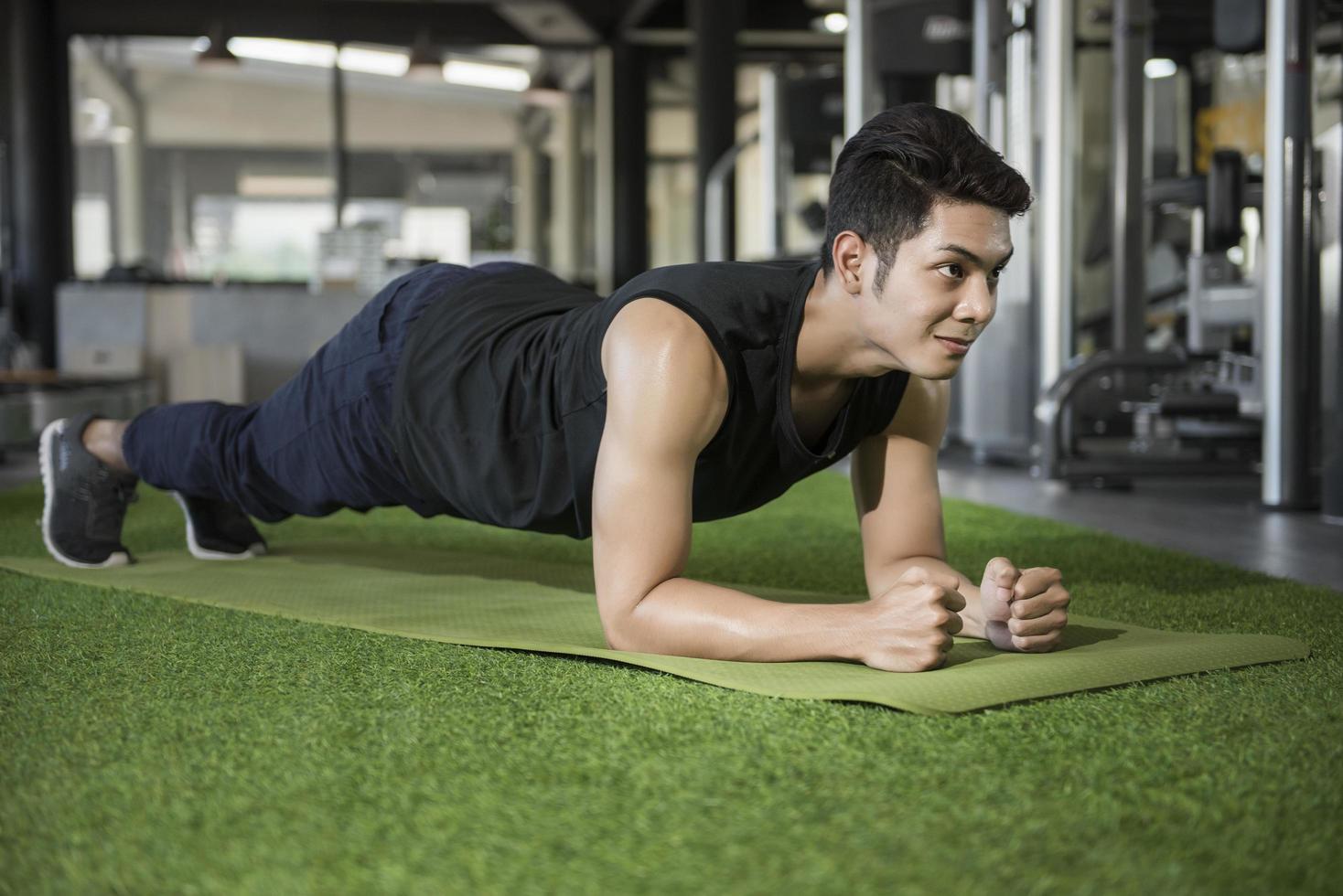 homem em prancha de ioga posar no ginásio foto