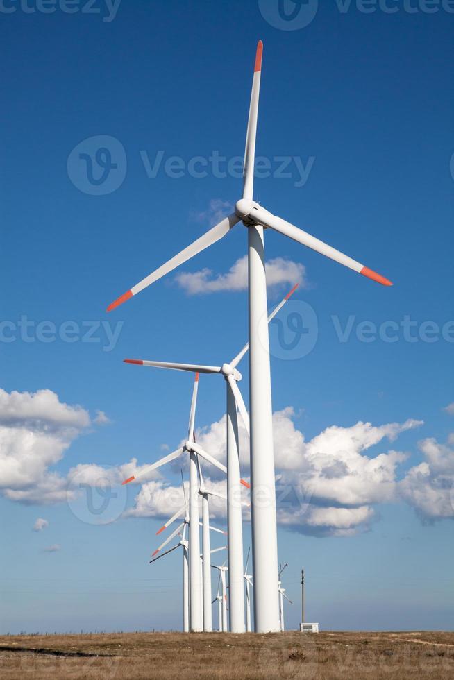 fazenda de turbinas eólicas sobre o céu azul nublado foto