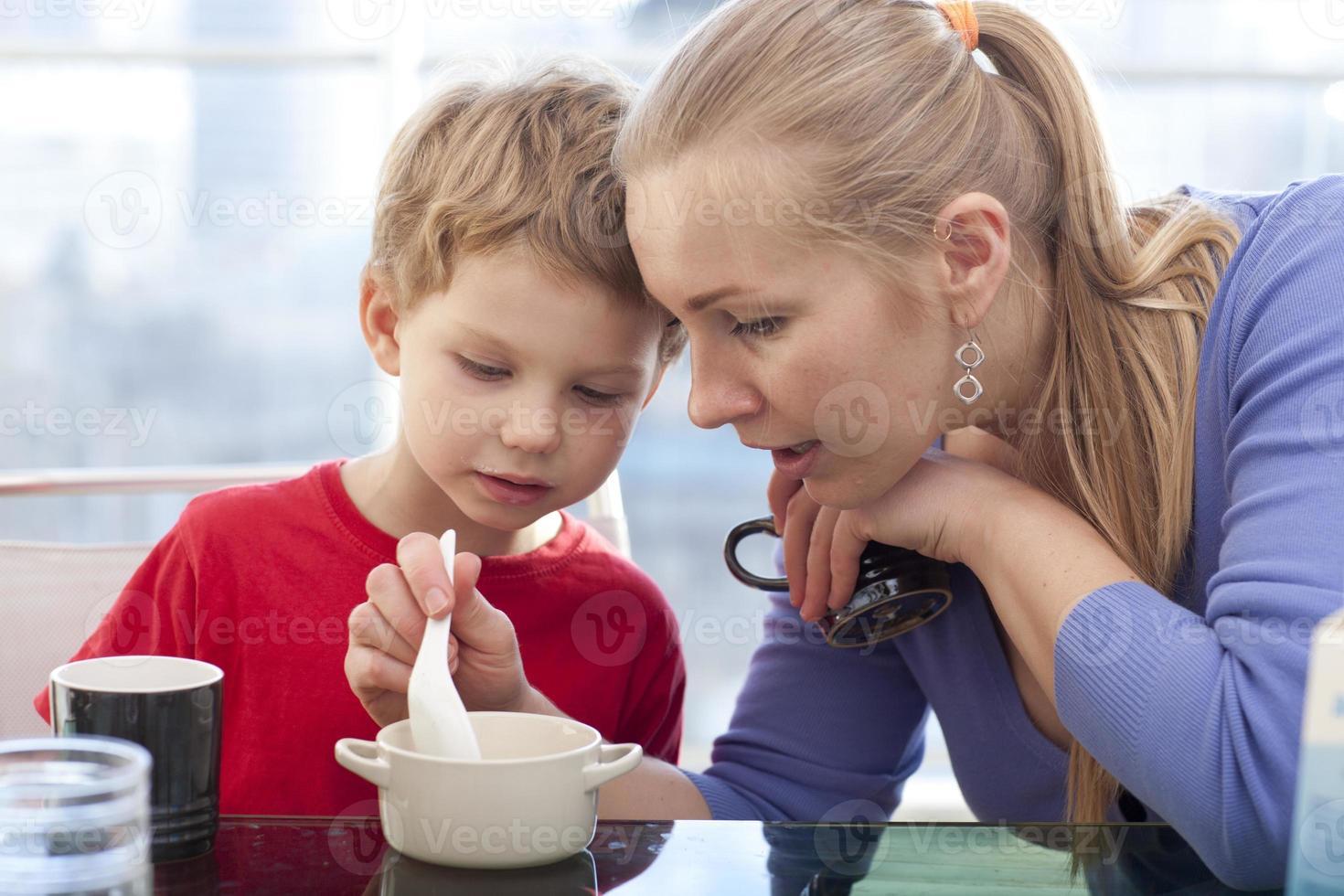 mãe e filho estão tomando café da manhã foto