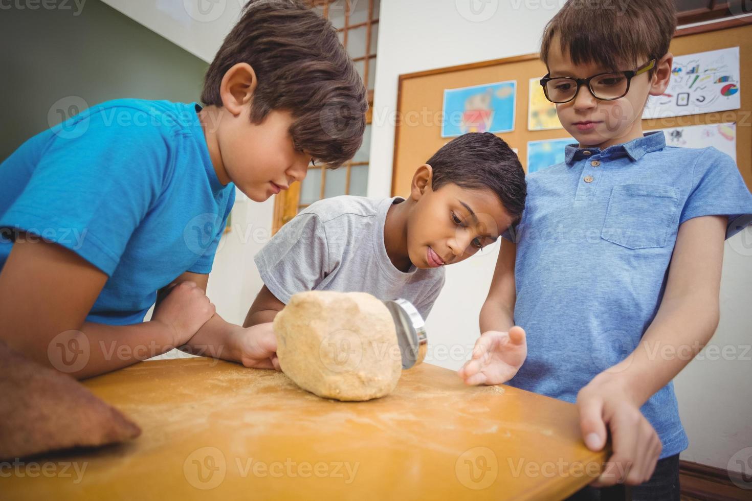 alunos olhando para uma pedra com uma lupa foto