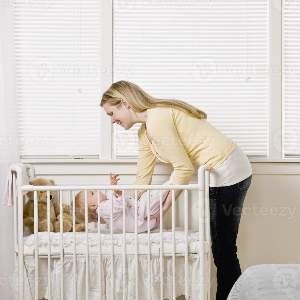 mãe colocando bebê no berço foto