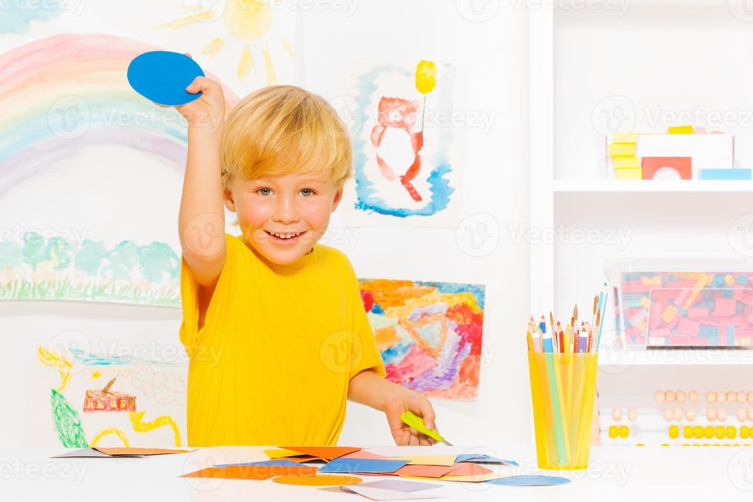 menino com cabelo loiro e círculo de papelão foto
