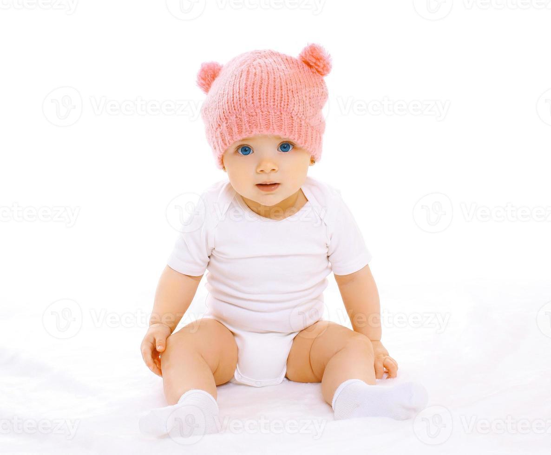 retrato de um doce bebê sentado com o chapéu de malha rosa foto