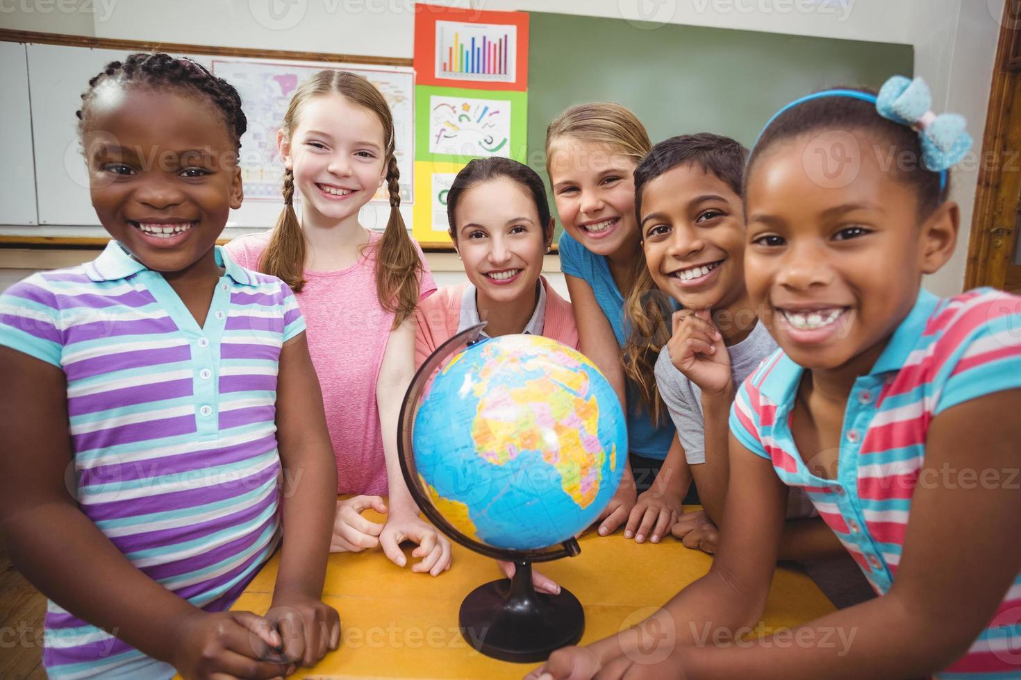 professor e alunos olhando para o globo foto