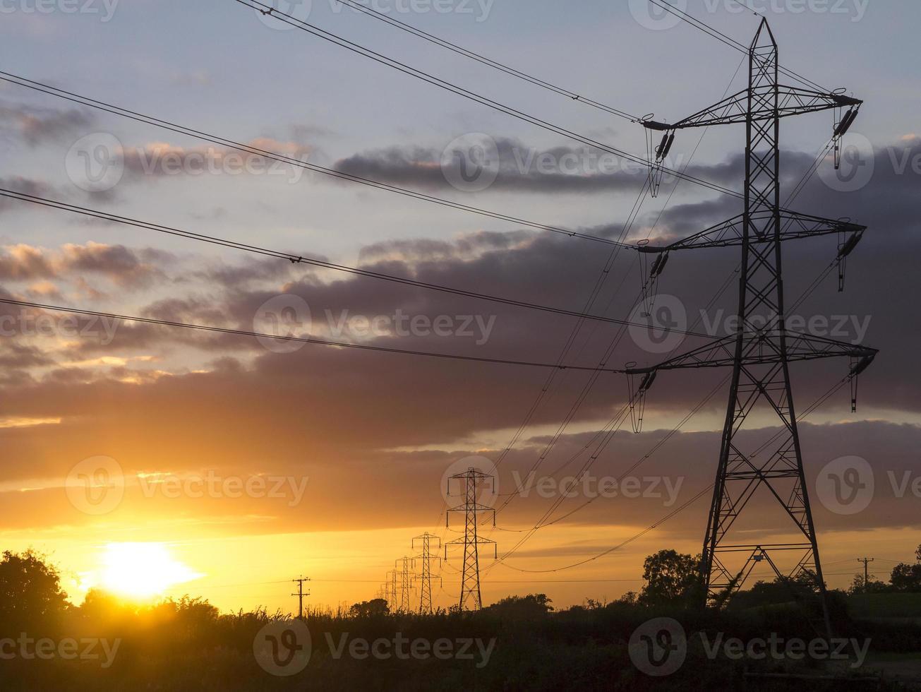 postes de eletricidade no campo ao anoitecer foto