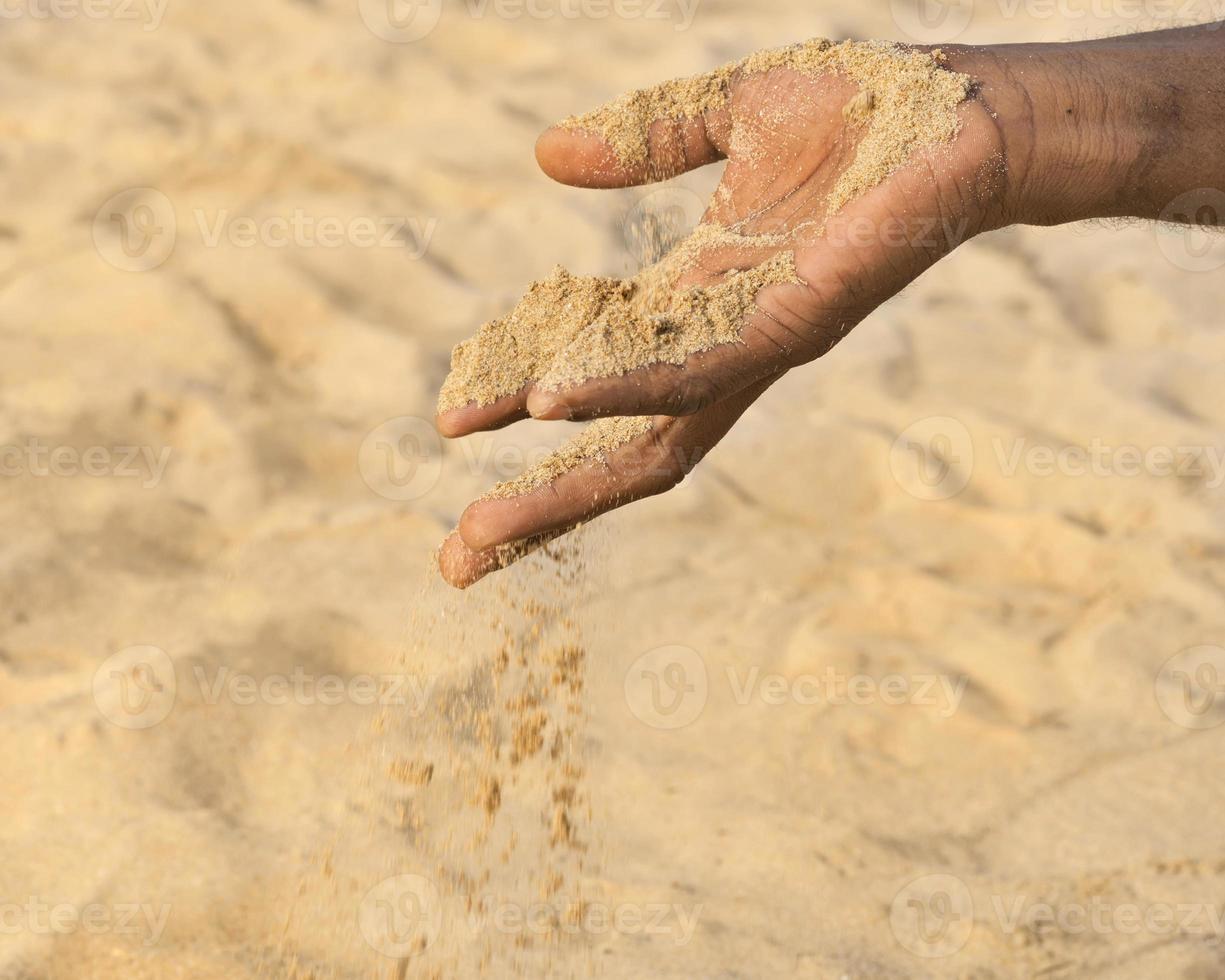 homem segurando um pouco de areia na mão: seca e desertificação foto
