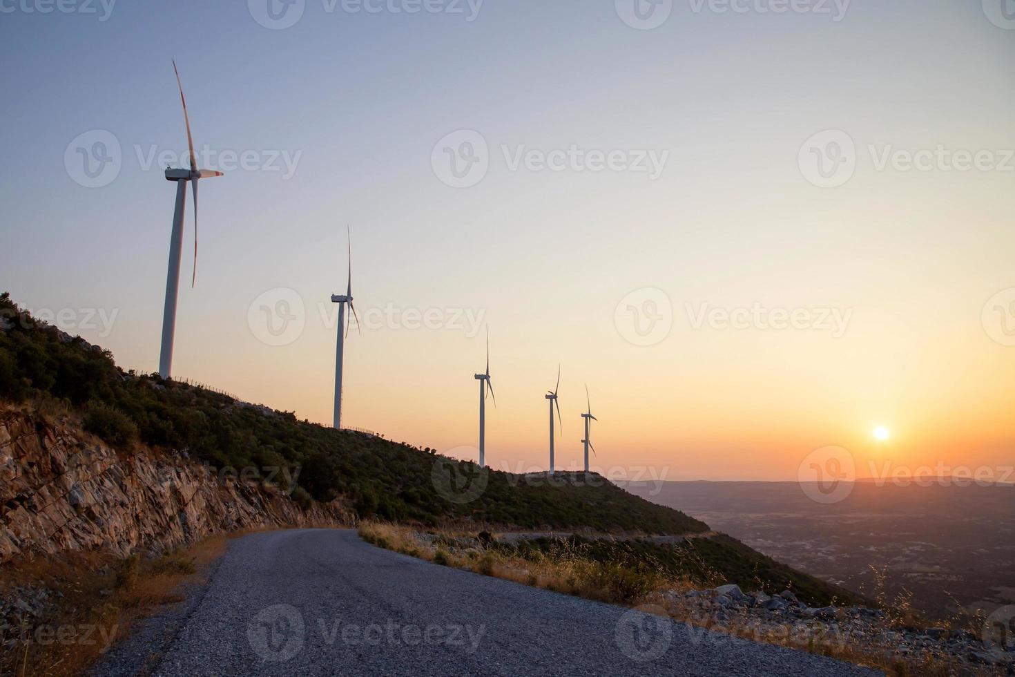 lindo pôr do sol com silhuetas de turbinas eólicas foto