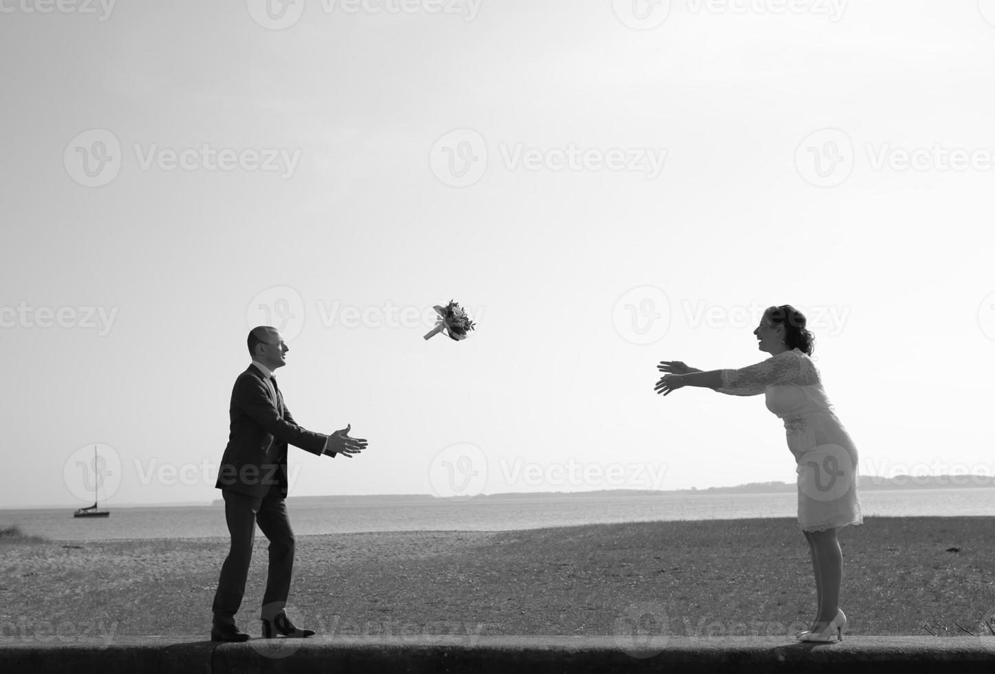 noiva e noivo no cais brincam com buquê de noiva. foto