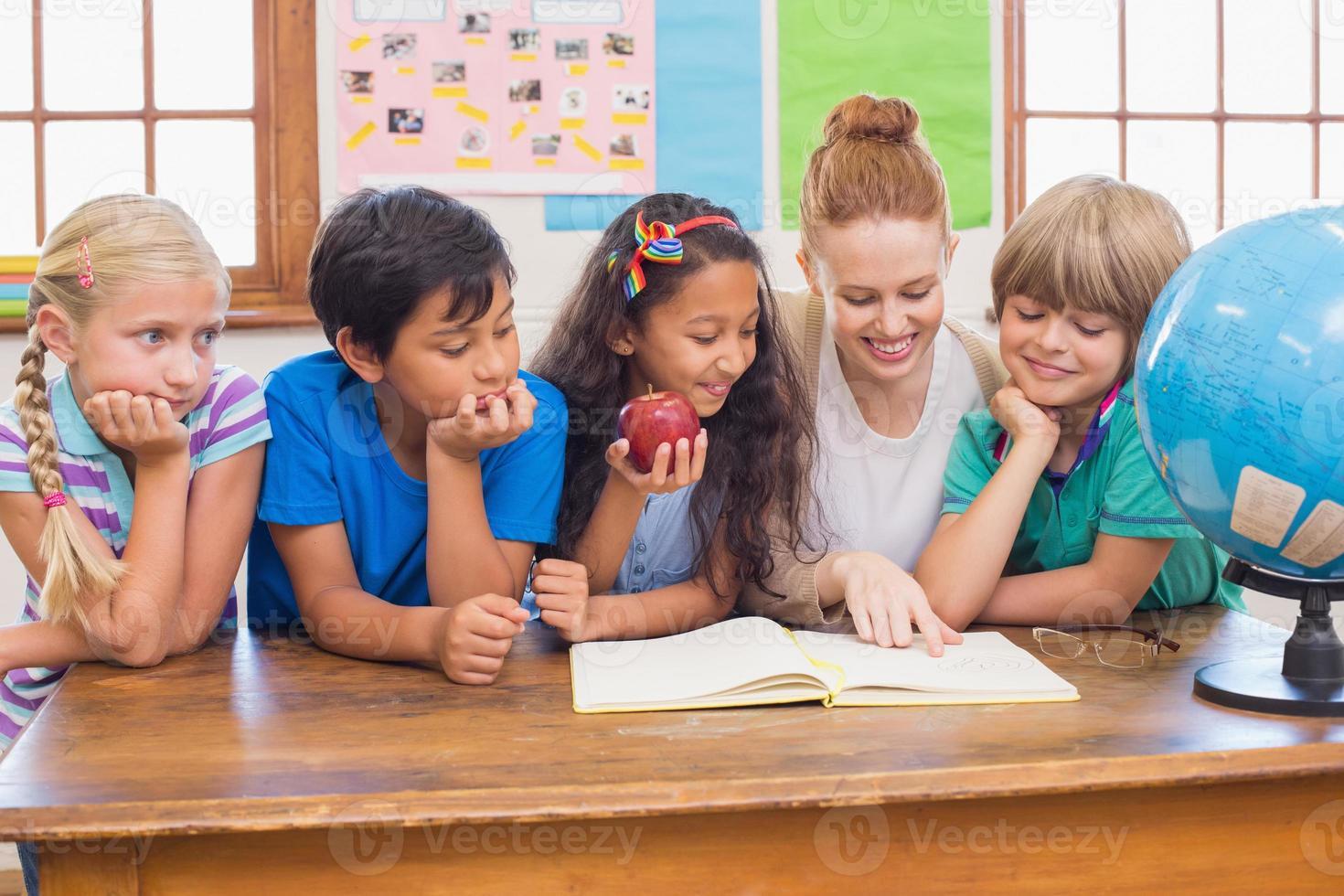 alunos fofos e professor sorrindo para a câmera na sala de aula foto