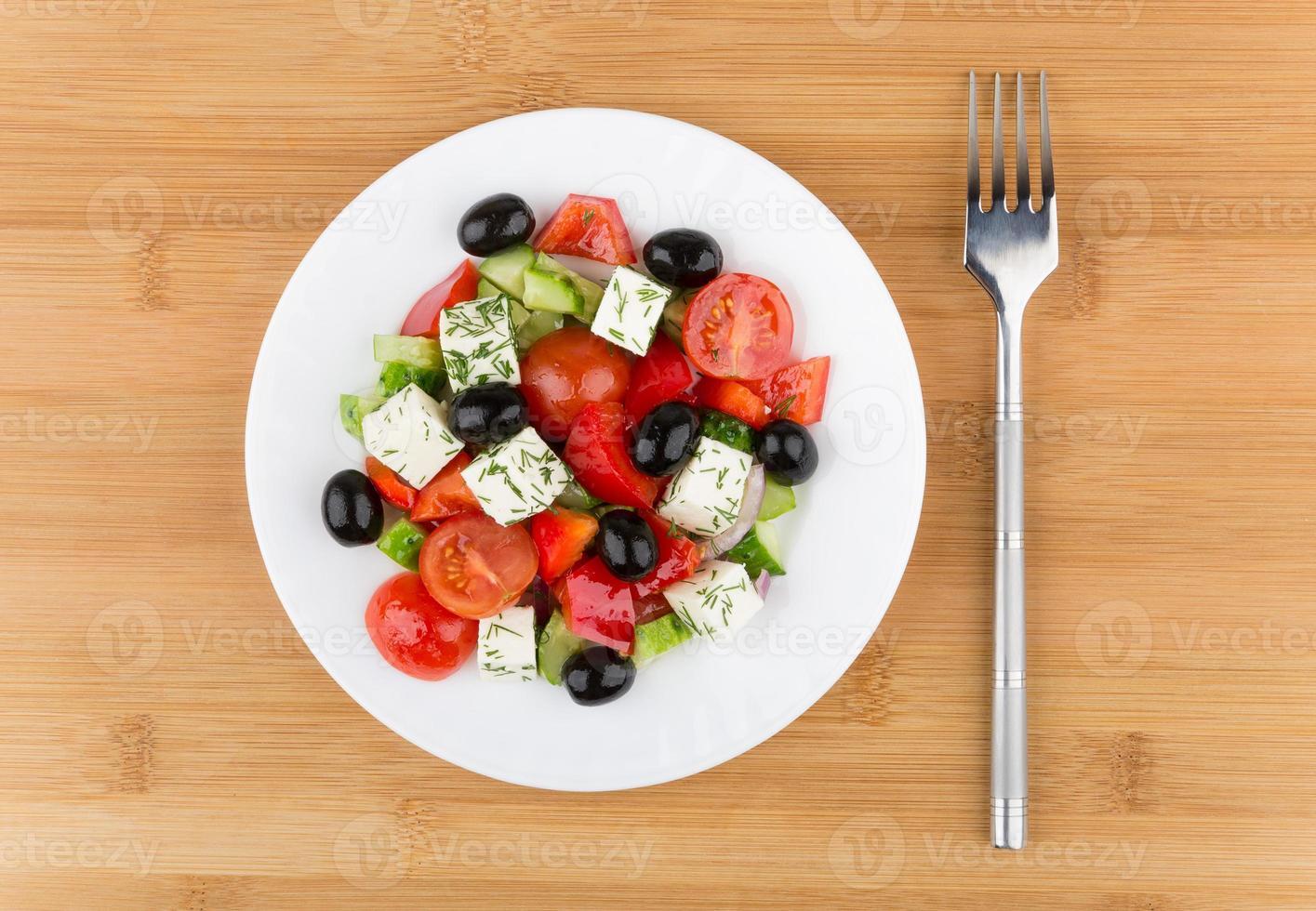 prato de vidro com salada grega e garfo na mesa de bambu foto