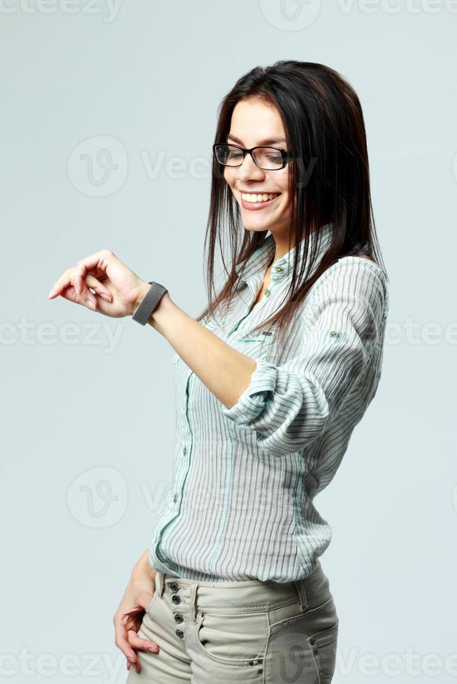 jovem empresária sorridente olhando para o relógio no pulso foto