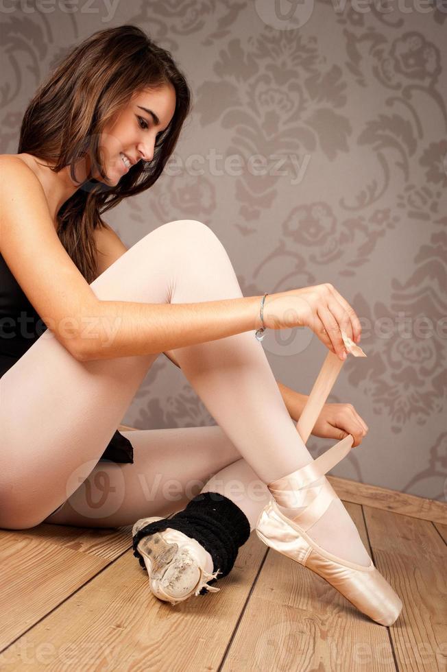 bailarina amarrando suas sapatilhas de balé foto