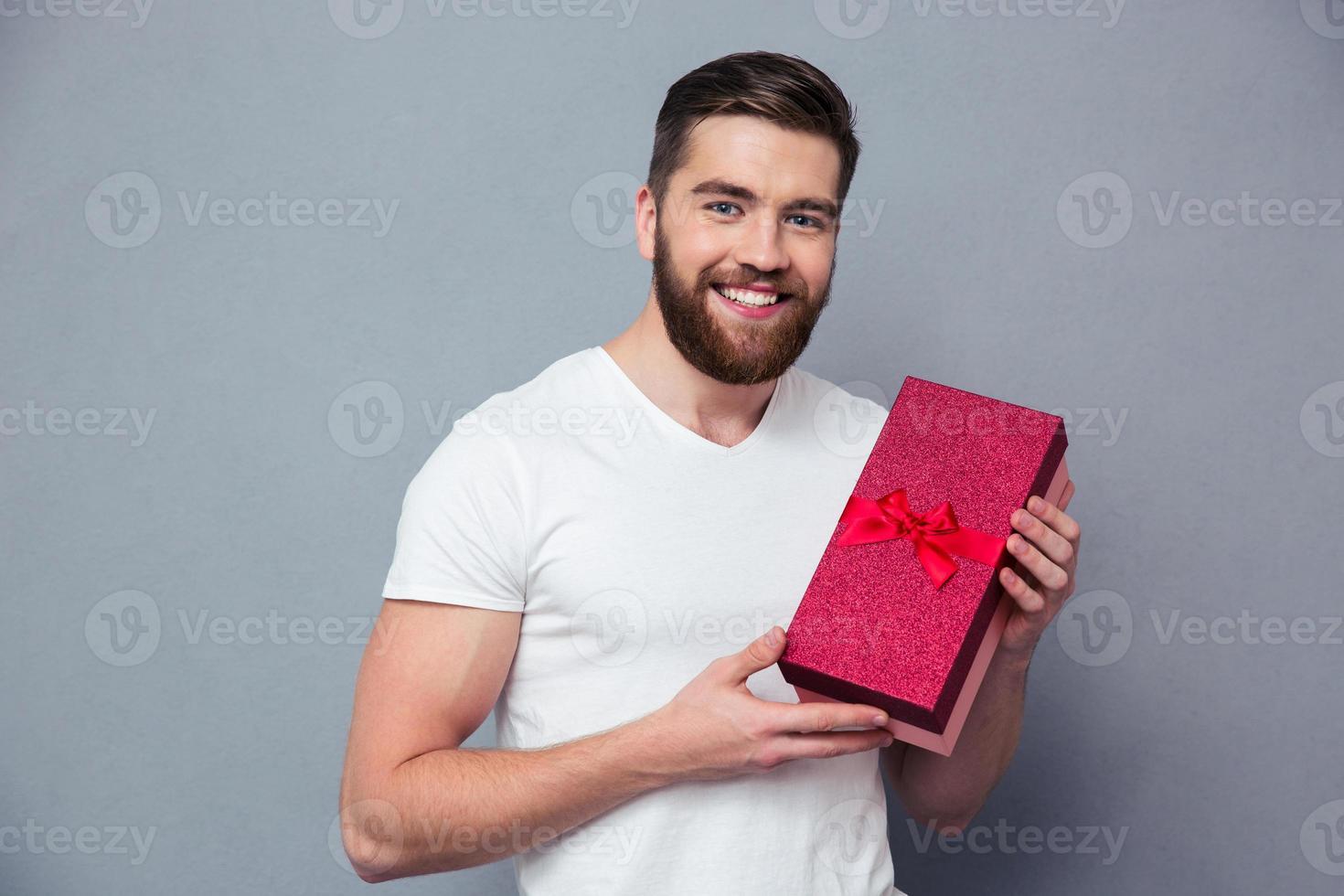 sorrindo casual homem segurando a caixa de presente foto