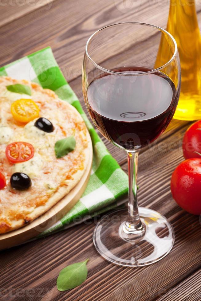 taça de vinho tinto e pizza italiana foto