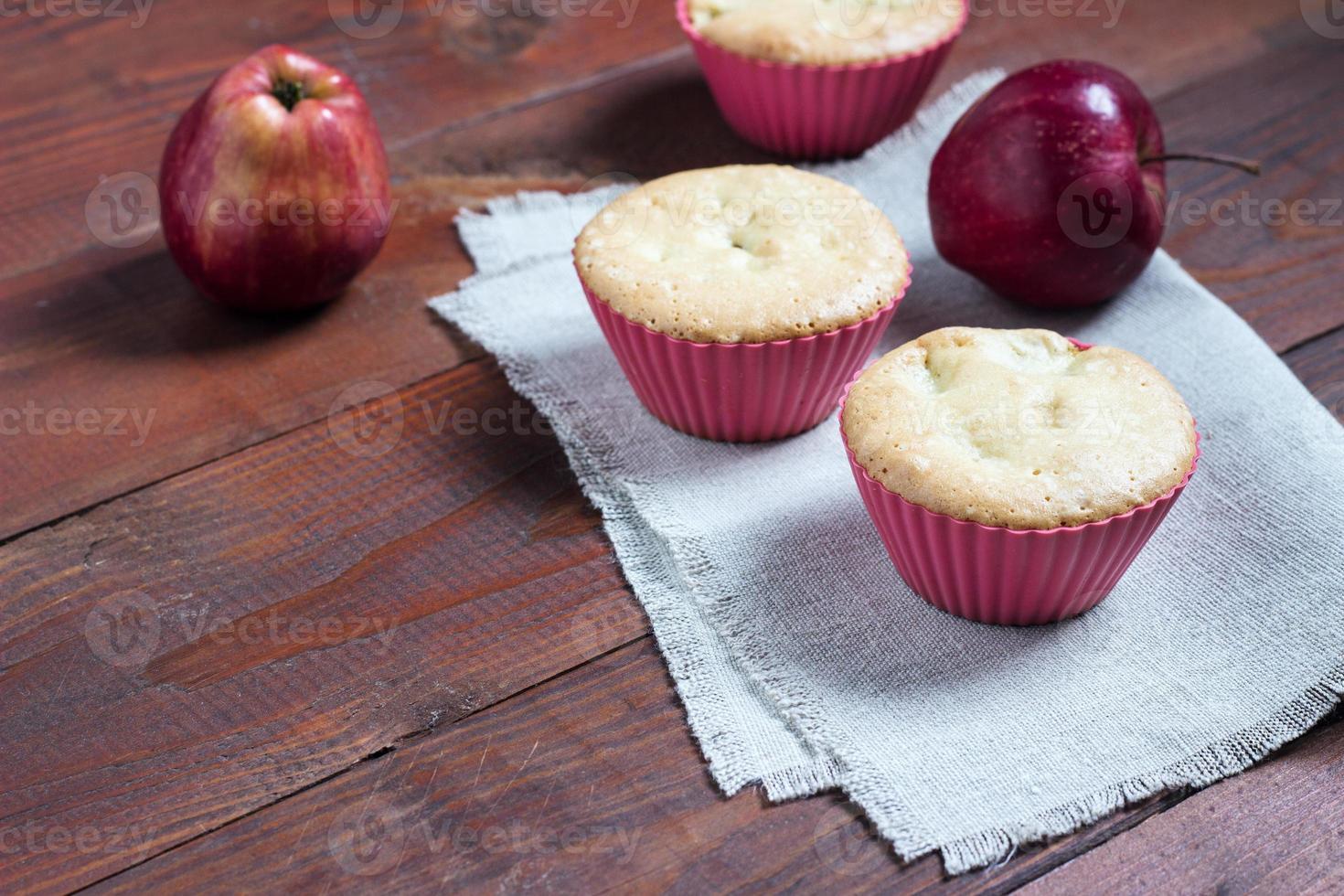 muffins de maçã frescos e quentes com maçãs no fundo foto