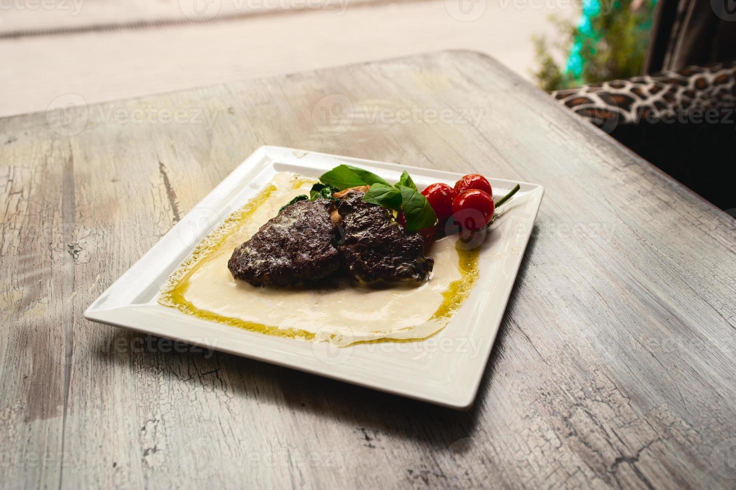 bife grelhado e cogumelos com tomate no prato branco foto