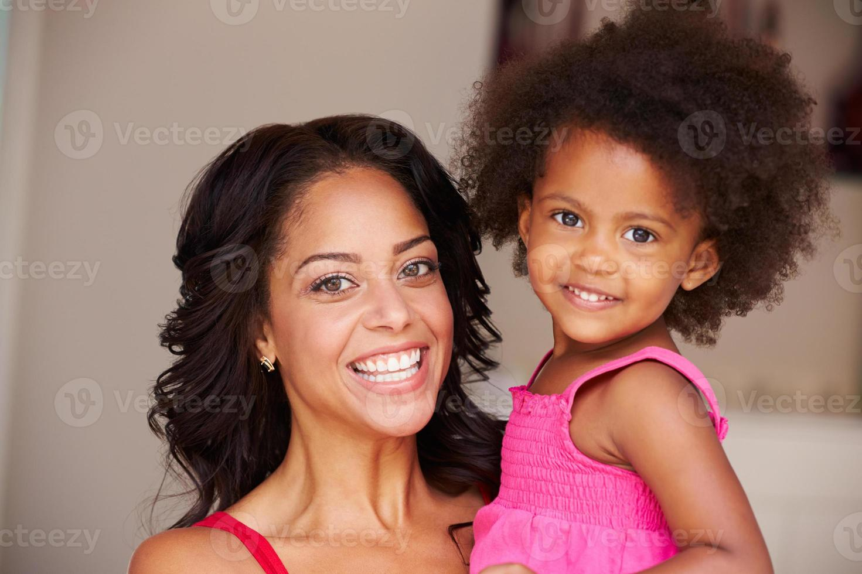 mãe afagando filha em casa foto