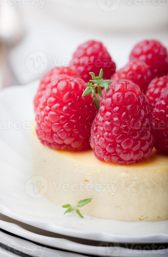 cheesecake com framboesas frescas em um prato branco. sobremesa. foto