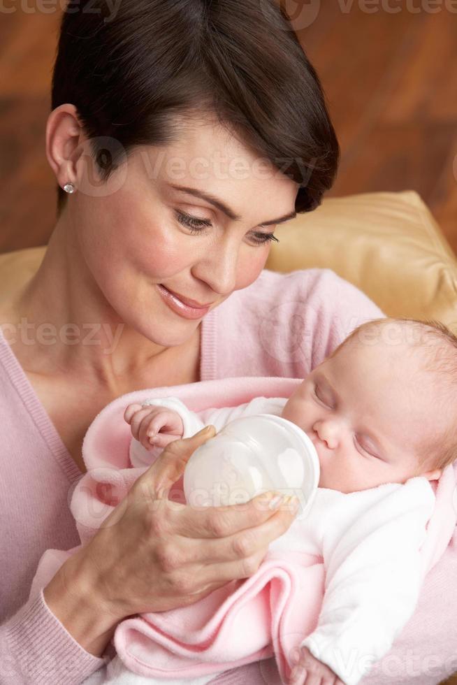 retrato de mãe alimentando bebê recém-nascido em casa foto