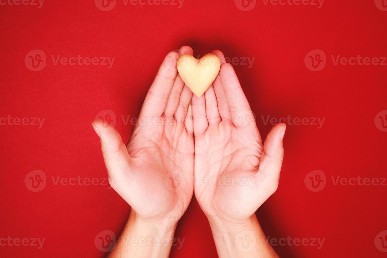 duas mãos segurando um pequeno coração de madeira genly foto