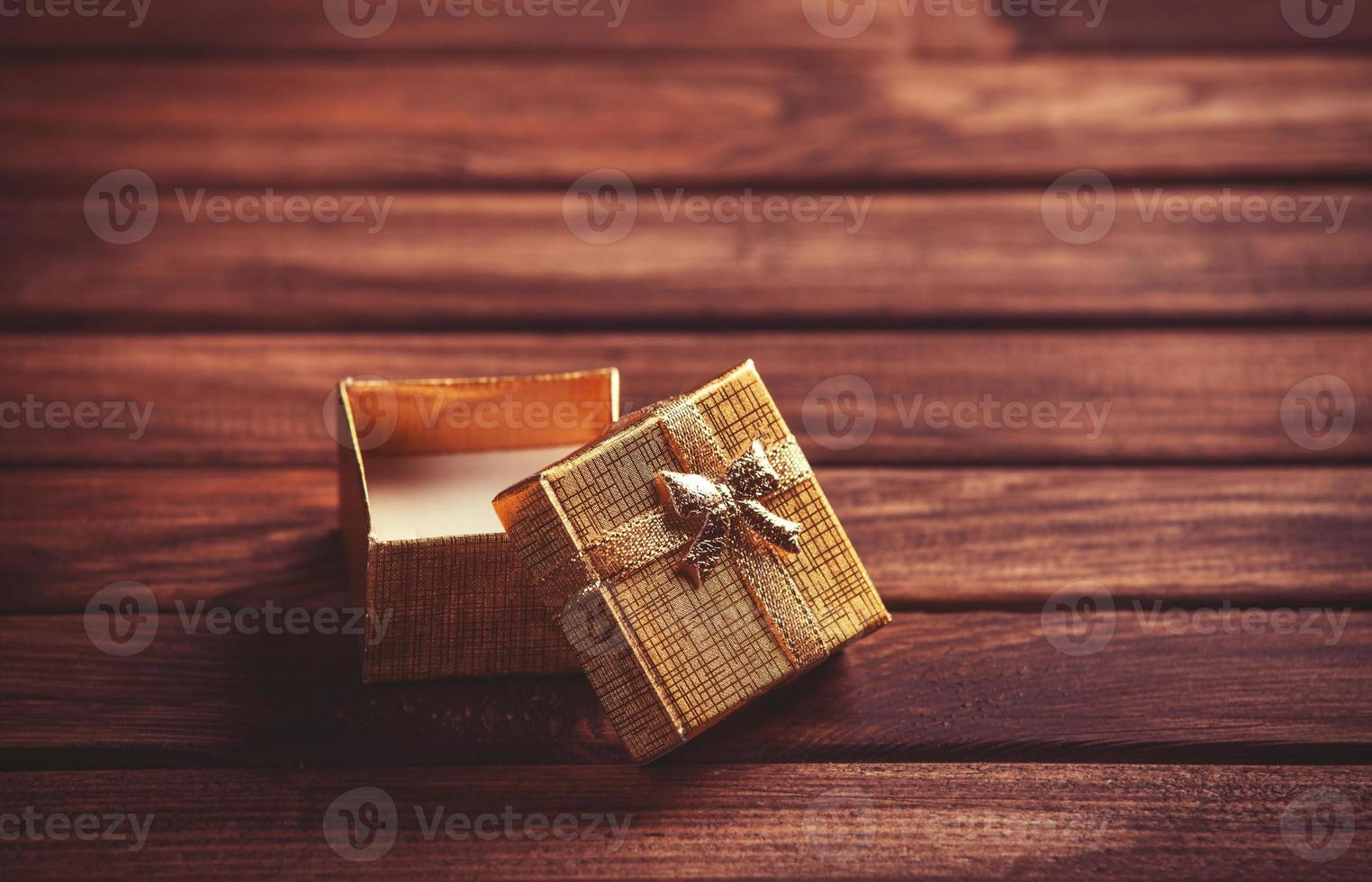 caixa de presente vermelha na mesa de madeira. foto