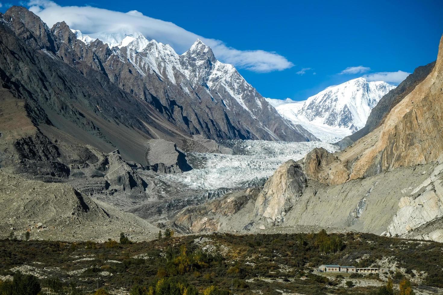 geleira passu cercada por montanhas cobertas de neve foto