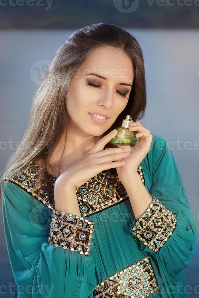 jovem segurando um frasco de perfume em uma paisagem à beira-mar foto