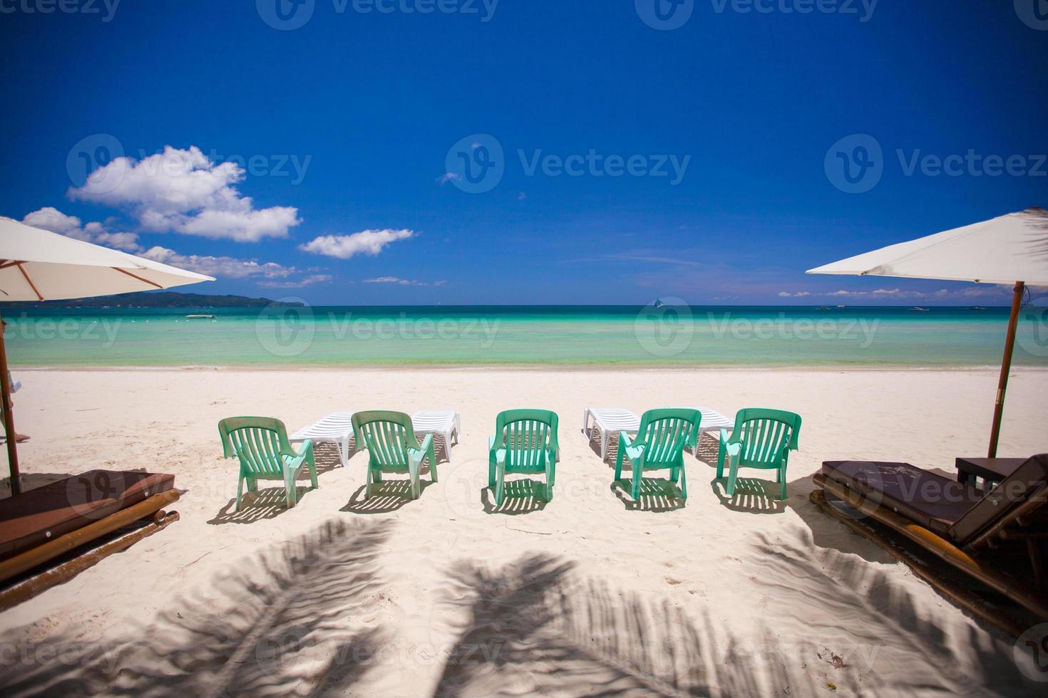 cadeiras na exótica praia tropical de areia branca foto