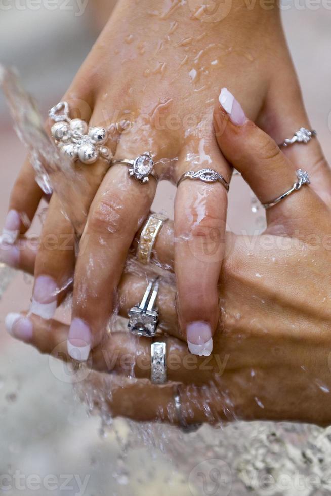 mulher lavando joias com as mãos cobertas de água foto