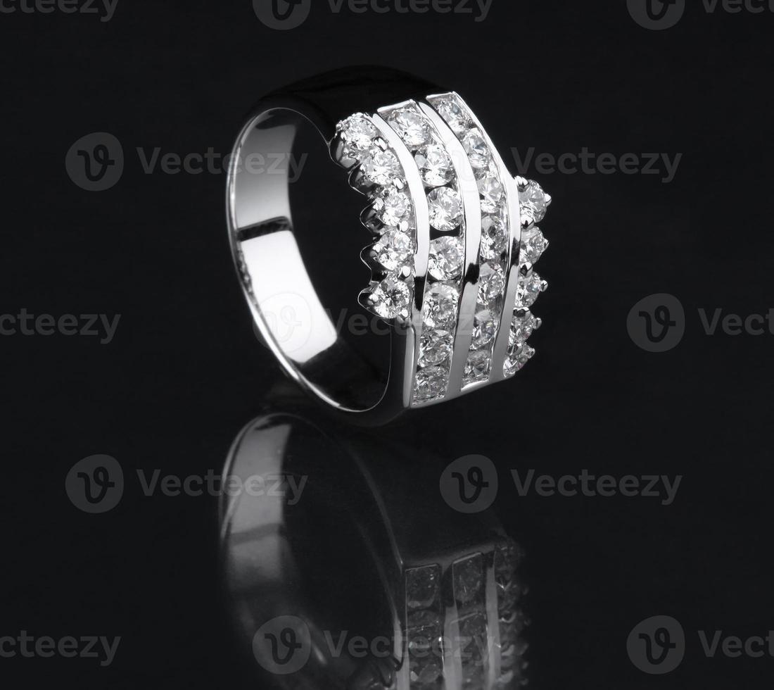 anel de diamante de ouro branco em fundo preto foto