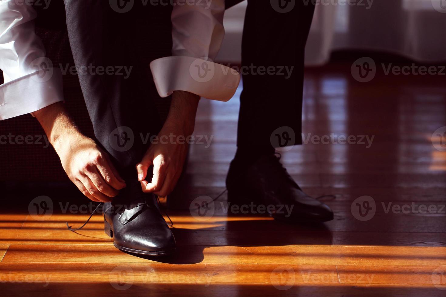 noivo amarrando o cordão em seu sapato de casamento foto