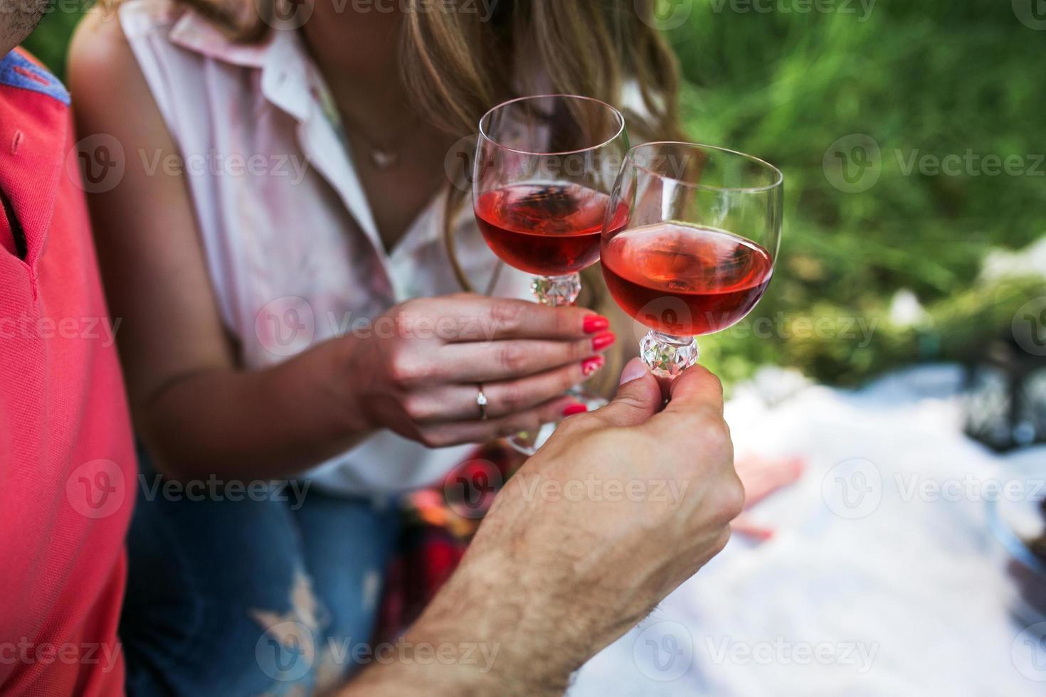 casal em um piquenique bebendo vinho e copos tilintando foto