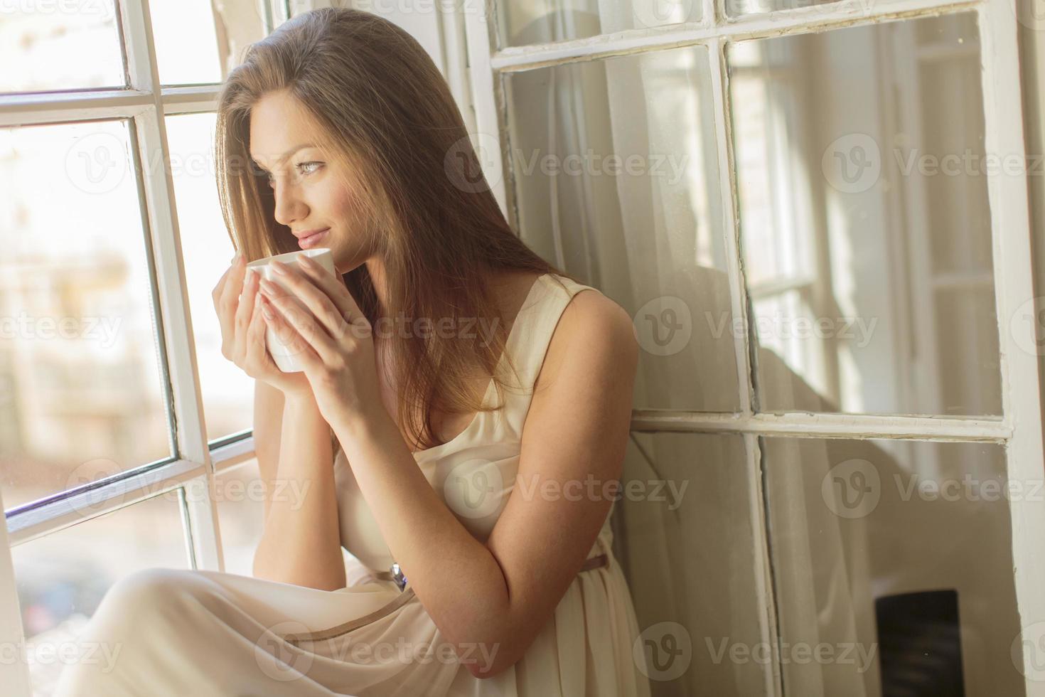 jovem bonita na janela foto