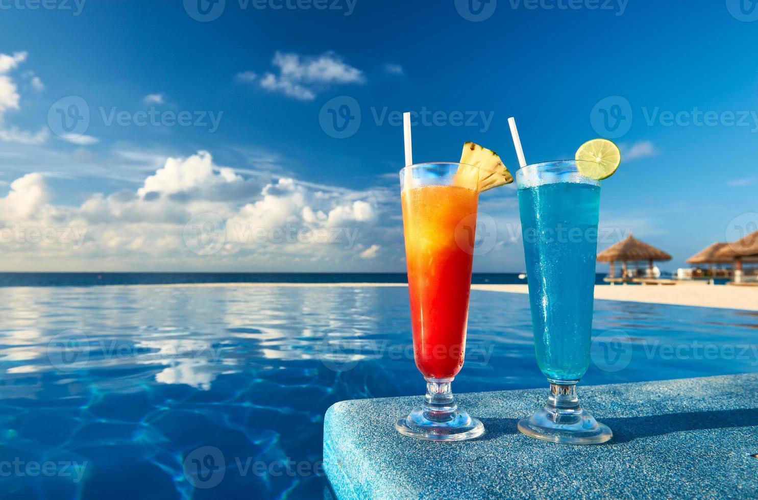 uma laranja e um coquetel azul na beira de uma piscina foto