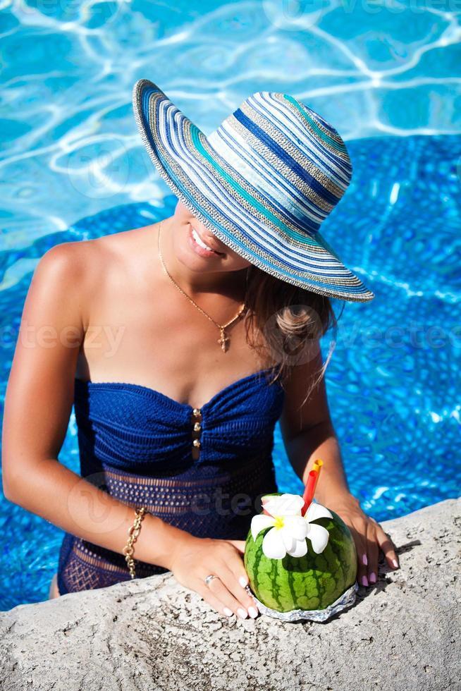 mulher de chapéu relaxando à beira da piscina com um coquetel exótico foto