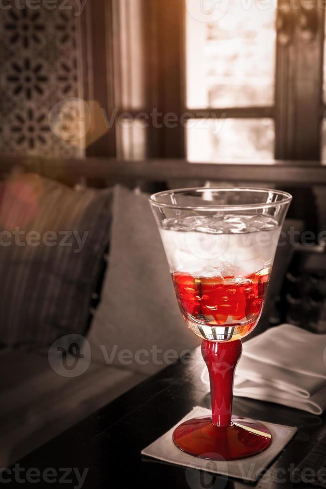 copo de água vermelho na mesa com luz do sol foto